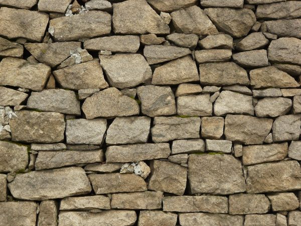 Wall texture of grey stones in various sizes placed loosely in uneven  formation. wall of loose stone 0063   Texturelib