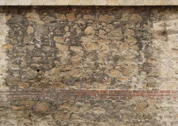 Tan Brick Wall Texture With Irregular Patches Of Whitewash And Dark Grey Cement Covering Its Surface
