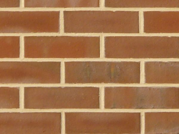 New red brick set in beige cement with faded white spots.