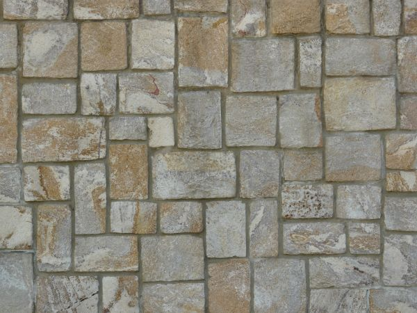 Evenly set multi-colored stone wall in dark grey grout.