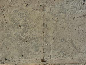 Concrete ground texture in grey and beige tones with very rough, worn surface.