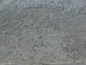 Concrete floor texture in light grey tone with very rough, inconsistent surface and brown dirt.