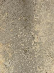 Irregular concrete floor texture in grey and light beige tone with very rough, worn surface.