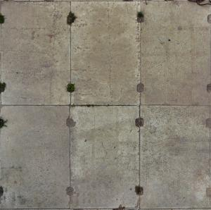Worn ground texture of concrete slabs in light grey tone with slightly worn surface and holes on edges.