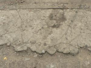 Worn concrete ground texture in light beige tone with very damaged, crumbling surface.
