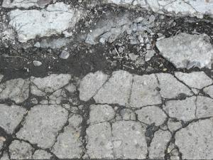Concrete floor texture in light grey tone with very damaged, cracked surface.