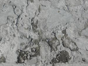 Concrete ground texture in light grey tone with extremely damaged, crumbling consistency.