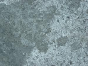 Rough concrete texture in mixed grey tones with irregular surface.