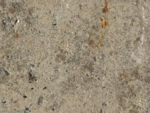 Beige concrete floor consisting of stones of mixed colors and sizes on surface.
