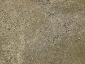 Rough concrete floor texture in light beige tone with small, grey rocks embedded in surface.