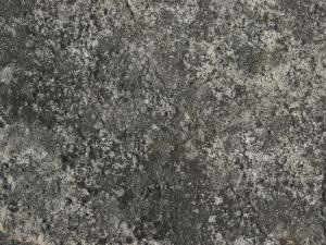 Concrete ground texture in dark grey tone with very rough, damaged surface.