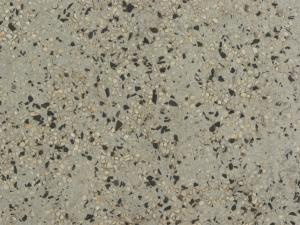 Rough, grey concrete texture with gravel of black and beige tones embedded into surface.