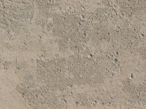 Texture of concrete floor in light beige color with slightly rough, flat surface.