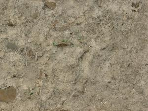 Ground of light brown concrete with extremely damaged, irregular surface and large stones.