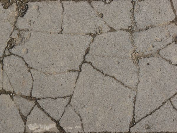 Texture Consisting Of Concrete In Light Grey Tone With Rough Surface And Cracks Throughout