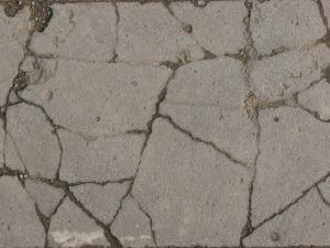Texture consisting of concrete in light grey tone with rough surface and cracks throughout.