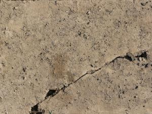 Concrete ground texture in beige color with some gravel on surface and large crack.
