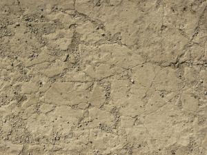 Worn concrete floor texture in beige color with very rough surface and cracks throughout.