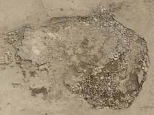 Concrete ground texture in light beige tone with very rough, damaged surface.