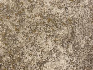 Concrete floor texture in mixed tones of grey and brown with rough surface.