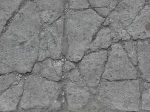 Old concrete floor texture in consistent, grey color with myriads of thick cracks throughout.