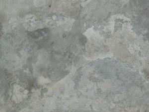 Smooth concrete floor texture in patches of different tones of grey.