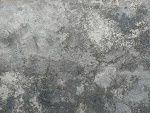 Concrete floor texture in mixed shades of grey with few, small cracks in surface.