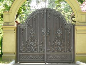 Grey Arching Metal Gates With Exquisite Designs Of Iron On Surface.