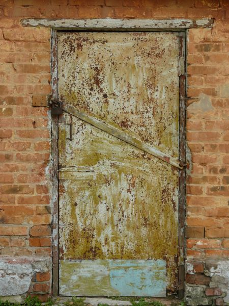 Old Metal Door With Rough Surface And Diagonal Metal Strip Across Middle.