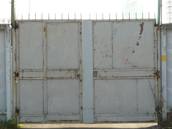 Large Metal Gates With Rust On Surface And Spikes Lining Top.