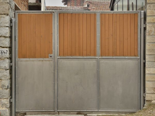 Grey Metal Gates With Wooden Plank Surfaces On Top Half Of Each Door.