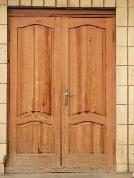 old wooden doors in light pink tone with gold metal handle