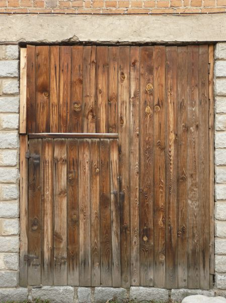 Elegant Large Wooden Doors Of Vertical Planks With Fading Bottom Edges.