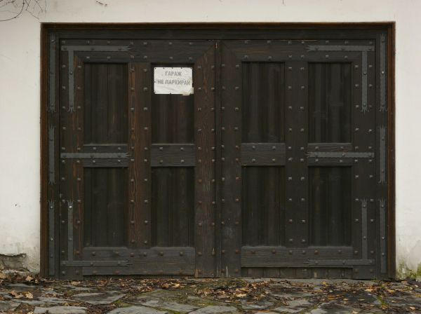 Large wooden garage doors in black tone large nails and white paper on