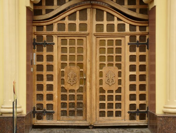 Large Wooden Doors With Square Pattern And Very Large Wooden Casing.