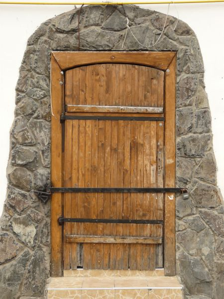 Aged Wooden Door With Stone Casing And Iron Crossbar In Front.