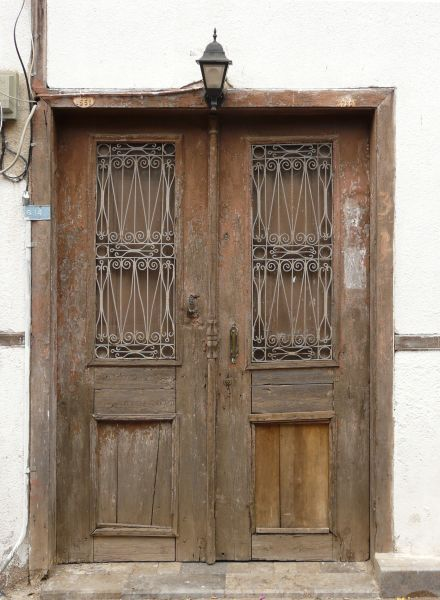 Charmant Aged Wooden Doors With Worn Surface And Iron Designs In Windows.