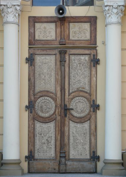 Old Double Doors With Exquisite Designs On Surface And Large Columns On  Sides.