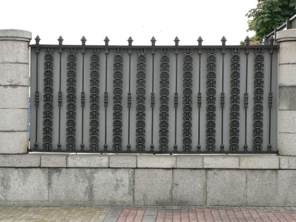 fence texture made up of iron bars cast in ornate floral patterns and set vertically