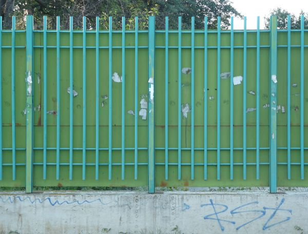 fence texture with blue painted bars set over a sheet of green metal various scratches