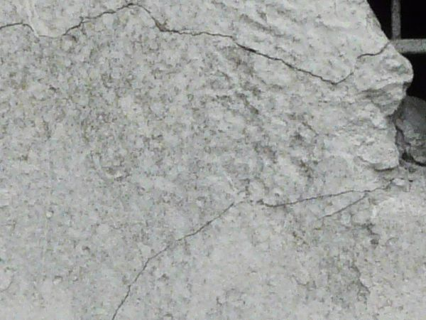 Concrete texture in white tone with very rough surface and large, deep cracks.