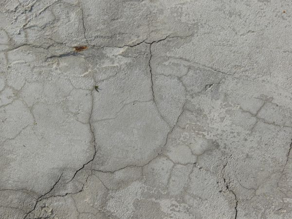 Concrete texture in light grey color with few, thin cracks in rough surface.