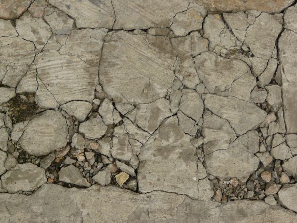 Concrete texture with very rough surface and cracked, crumbling surface.