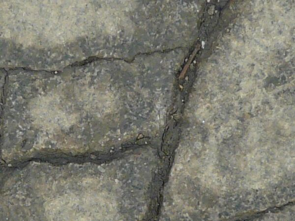 Texture of concrete in grey tone with large, dark cracks in surface.