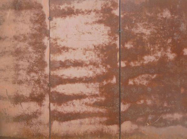 metal texture of large panels in red tone with large spots of fading paint and rust