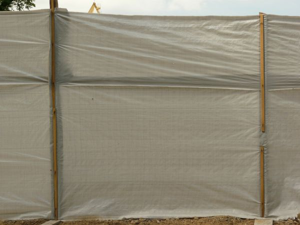 plastic tarp in grey tone with wrinkles and tears stretched between wooden posts
