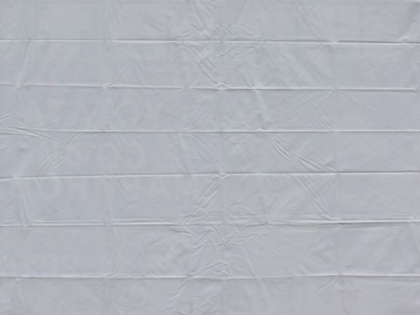 thin plastic tarp in white color with creases and wrinkles on surface