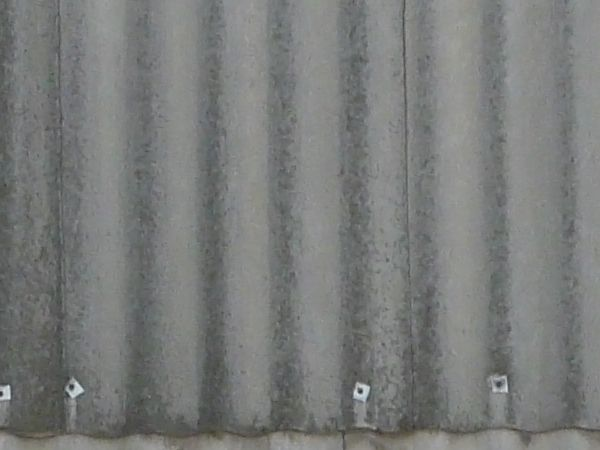 Roofing made of grey sheet metal with wave-like texture.