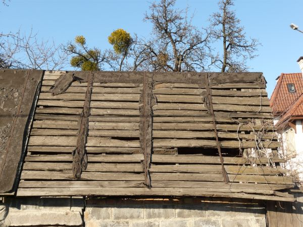 Very old, decrepit roof of wooden planks with splintering edges and large  holes.