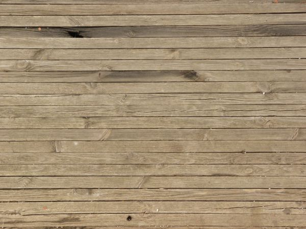 Tan wooden plank flooring with cracks and holes.